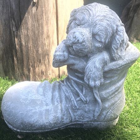 puppy sleeping in a boot cement garden art
